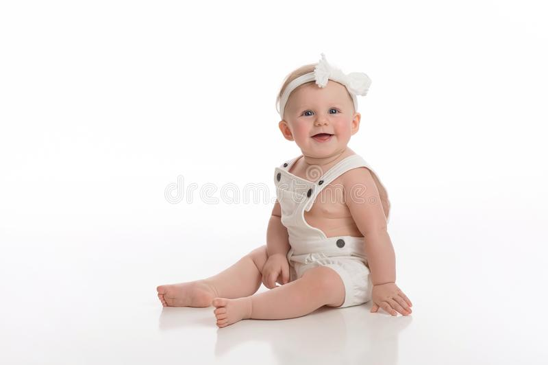 Att le behandla som ett barn bärande vita overaller för flickan royaltyfri foto