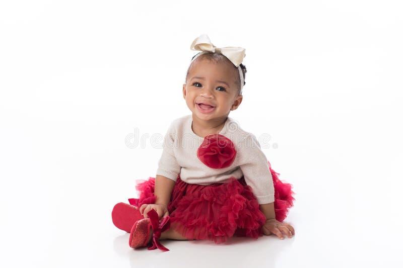 Att le behandla som ett barn flickan som bär en röd ballerinakjol royaltyfri fotografi