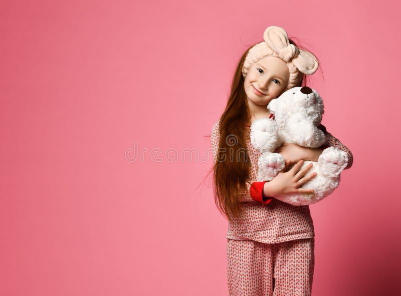 Att le behandla som ett barn flickan som rymmer en vit nallebj?rn i rummet en rosa bakgrund royaltyfri bild