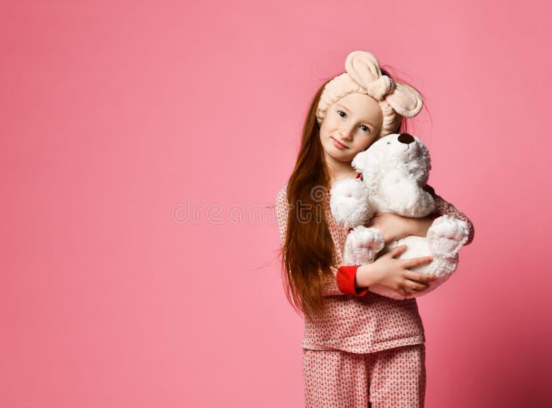 Att le behandla som ett barn flickan som rymmer en vit nallebj?rn i rummet en rosa bakgrund arkivfoto