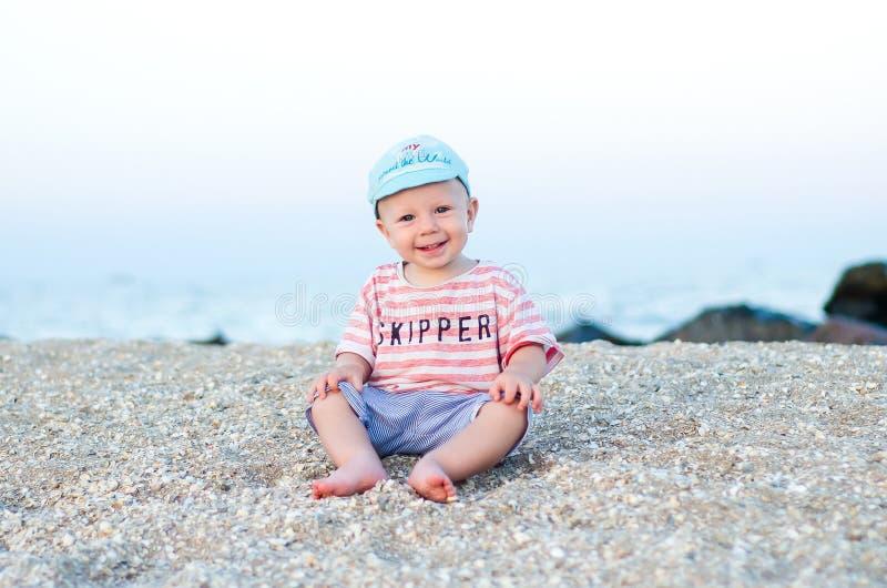 Att le behandla som ett barn pojkesammanträde på sanden nära havet sommar för snäckskal för sand för bakgrundsbegreppsram Ferie s arkivfoto