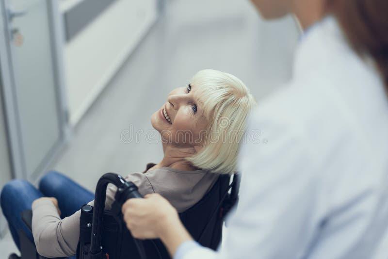 Att le den åldriga damen på pushchairen är att tycka om läkarehjälp royaltyfria bilder