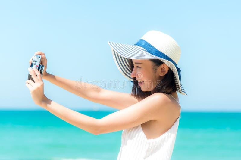 Att le den asiatiska kvinnan som använder kameran som gör självståenden med den lyckliga framsidan på stranden, kopplar av och de royaltyfria bilder