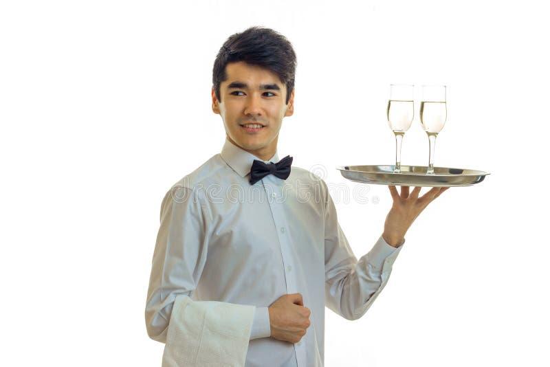 Att le den attraktiva uppassaren är rakt, och lyftt in räcka ett magasin med exponeringsglas av vinnärbild som isoleras på vit arkivbilder