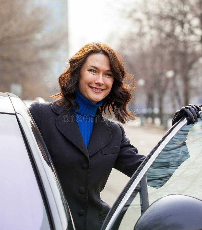 Att le den europeiska medelåldersa kvinnan sitter i bilen royaltyfria foton