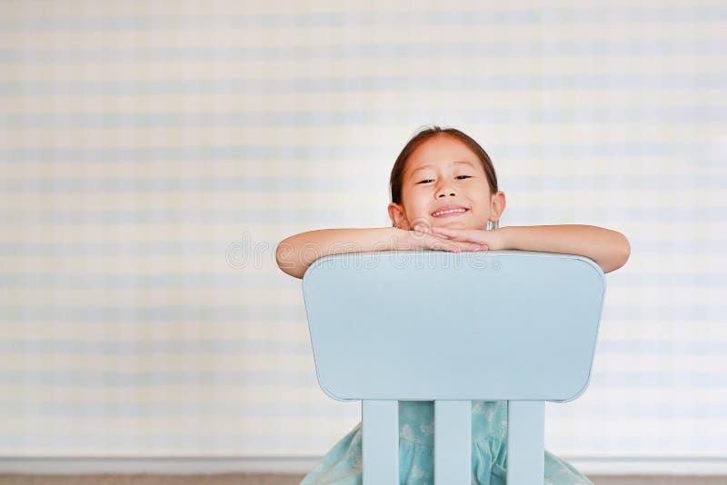 Att le den förskole- flickan för det lilla asiatiska barnet i ett dagisrum poserar på plast- behandla som ett barn stol arkivfoton