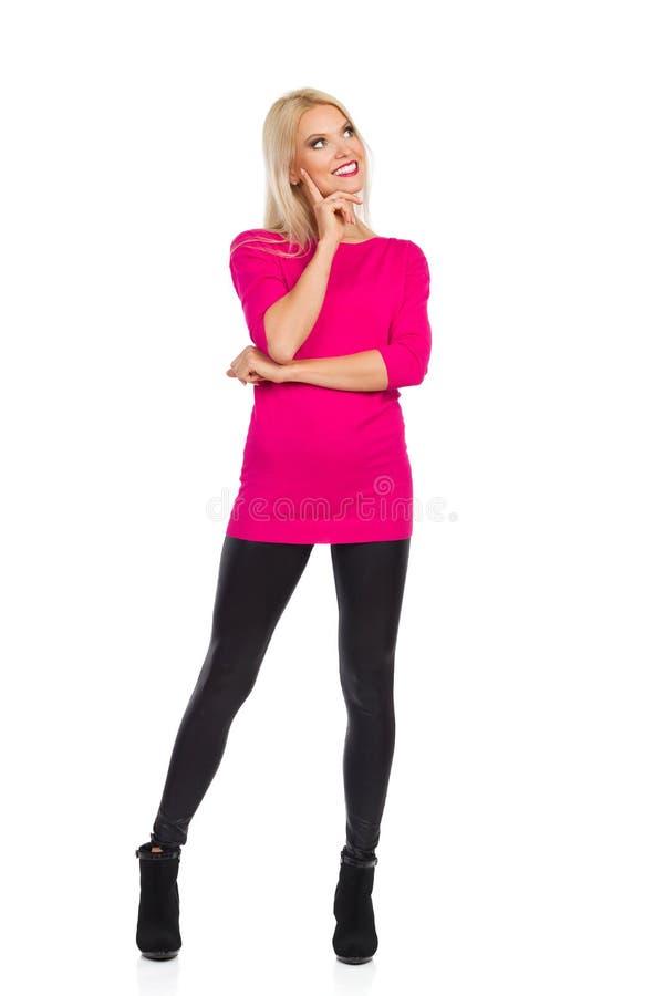 Att le den härliga blonda kvinnan står med handen på hakan och att se bort och att tänka royaltyfri bild