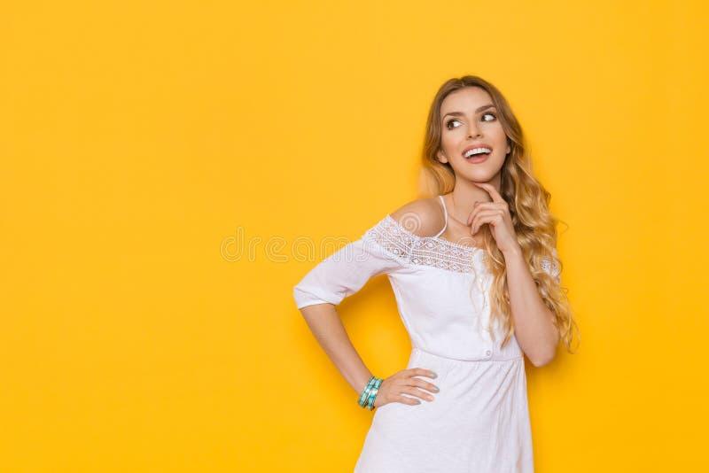 Att le den härliga blonda unga kvinnan i den vita sommarklänningen ser bort och att tänka fotografering för bildbyråer