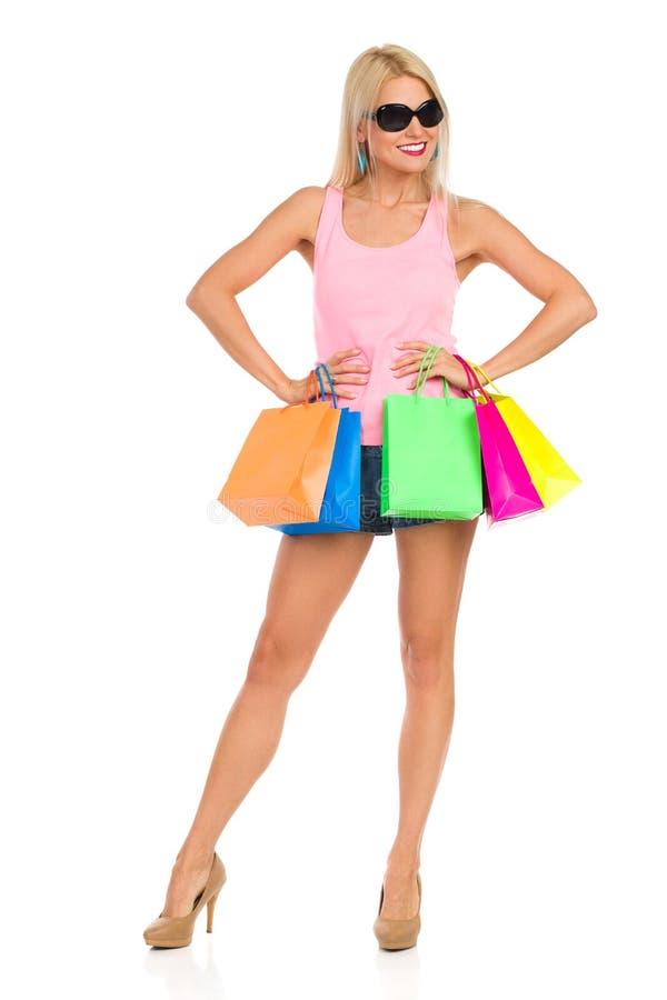 Att le den härliga kvinnan poserar med färgrika shoppingpåsar royaltyfria bilder