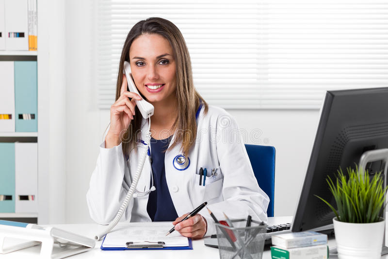 Att le den kvinnliga doktorn satt på skrivbordet med telefonen för att gå i ax arkivfoto