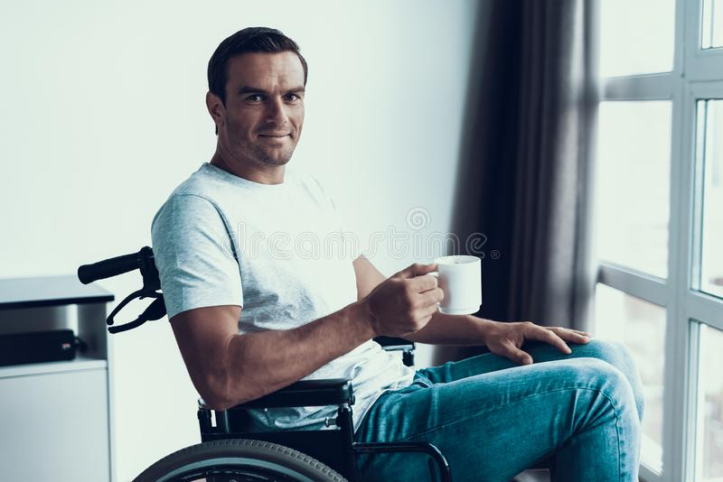 Att le den rörelsehindrade mannen sitter i rullstol med koppen royaltyfri foto