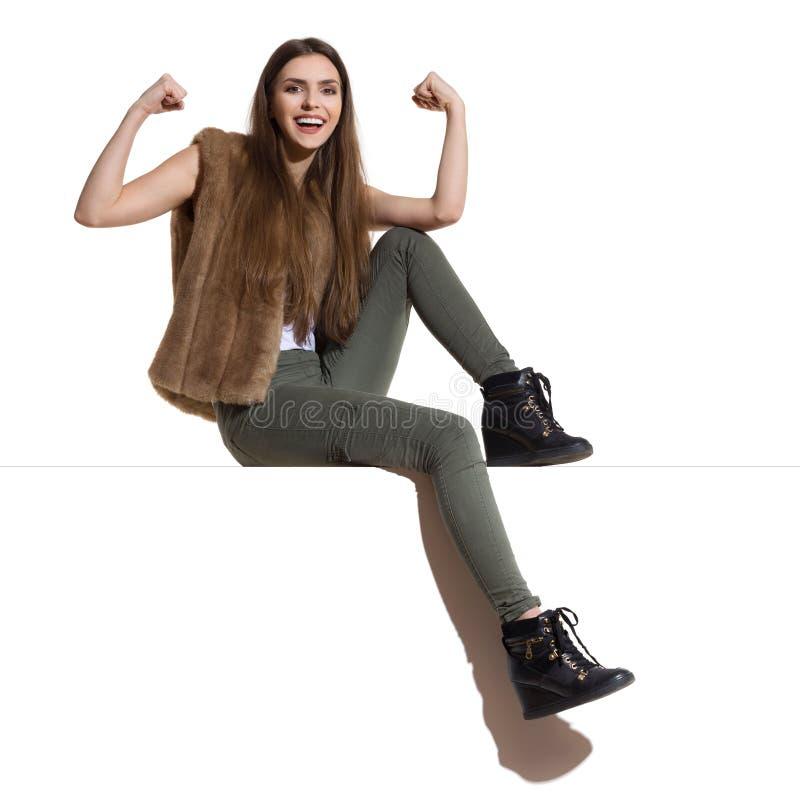 Att le den tillfälliga kvinnan sitter på en överkant och att böja muskler arkivfoto