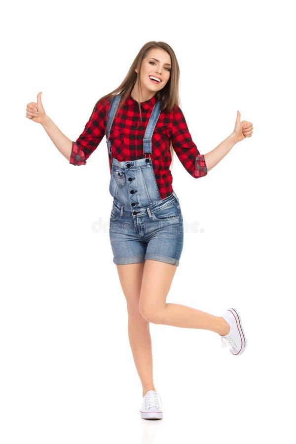 Att le den tillfälliga kvinnan står på ett ben och visar upp tummar arkivbilder