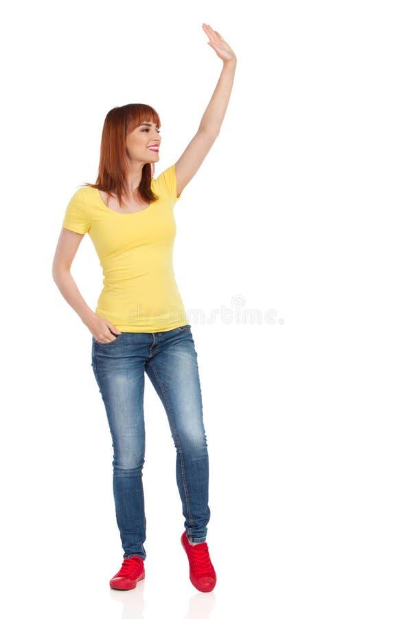 Att le den tillfälliga unga kvinnan står den vinkande handen och ser bort arkivbilder