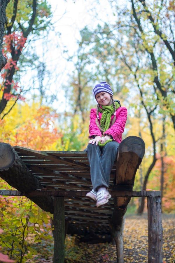 Att le den tonårs- flickan sitter i höstskogen arkivfoton