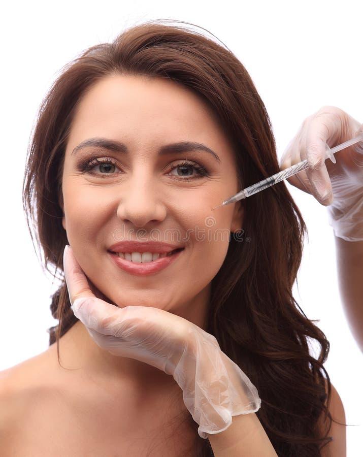 Att le den unga kvinnan får kosmetiska injektioner i ckeek som isoleras över vit bakgrund Doktorshänder som gör en injektion i fr arkivfoton