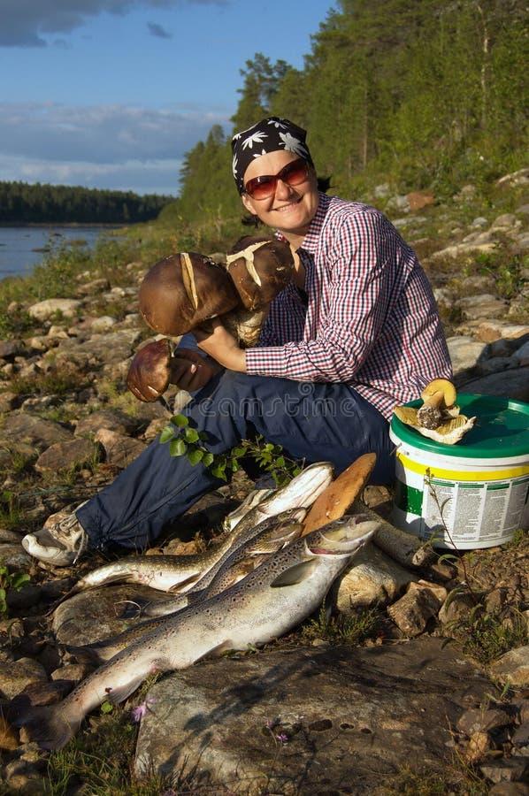 Att le den unga kvinnan med gåvor av naturen sitter på banken av den nordliga floden arkivfoton
