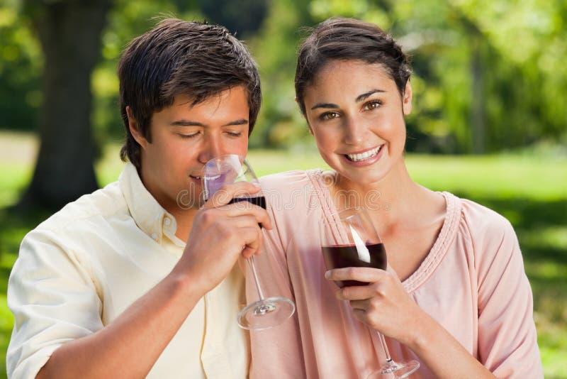 Att le för kvinna fördriver som henne, dricker vännen wine arkivbild