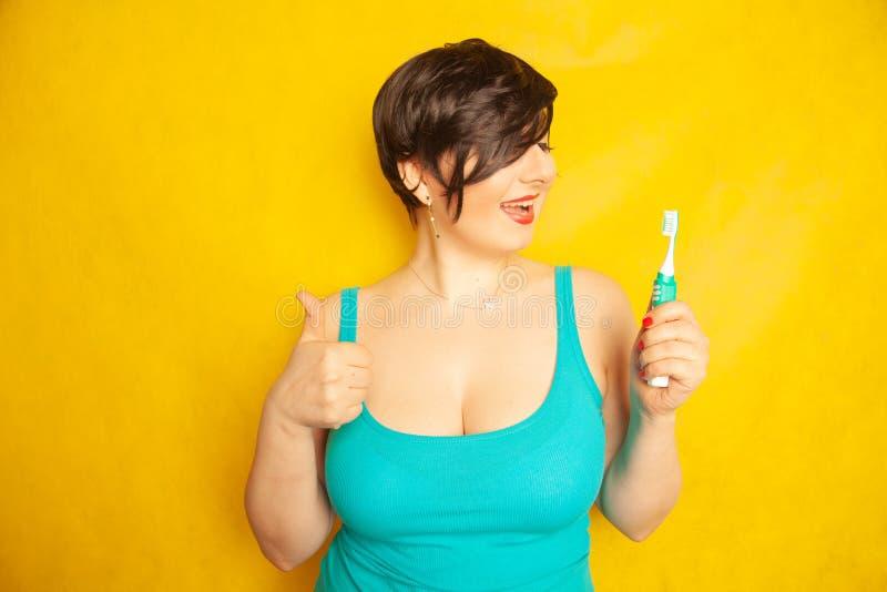 Att le flickan med kort hår och ett curvy diagram står med en tandborste i hennes händer på gul fast studiobakgrund royaltyfri bild
