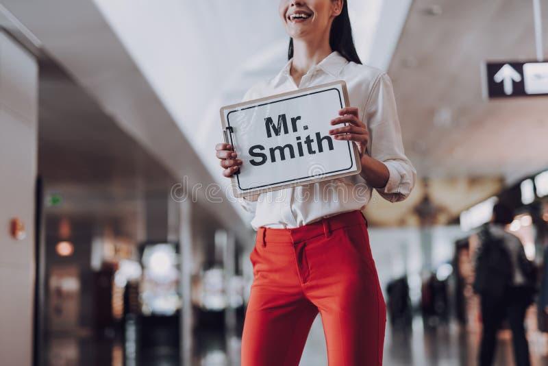 Att le flickan väntar på besökaren med tecknet på flygplatsen fotografering för bildbyråer