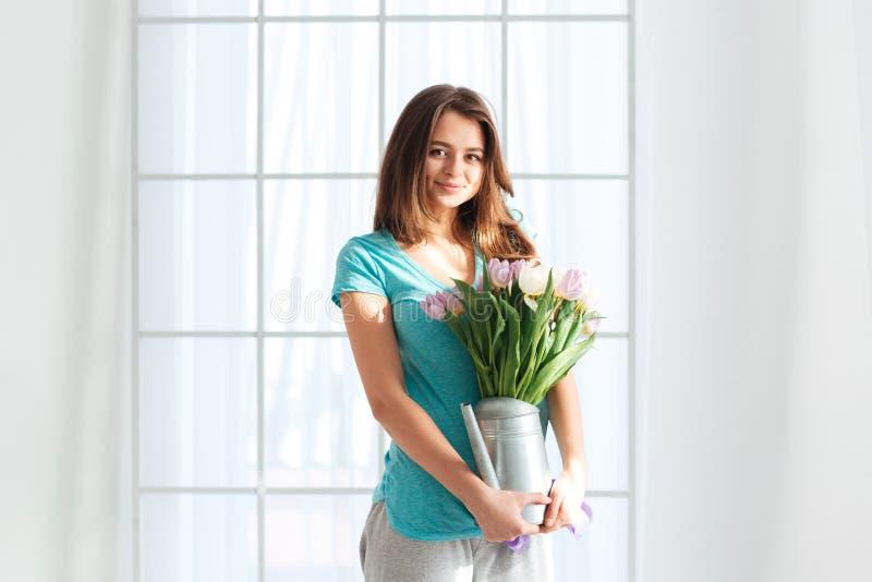 Att le innehavet för den unga kvinnan som bevattnar kan med buketten av blommor royaltyfria bilder