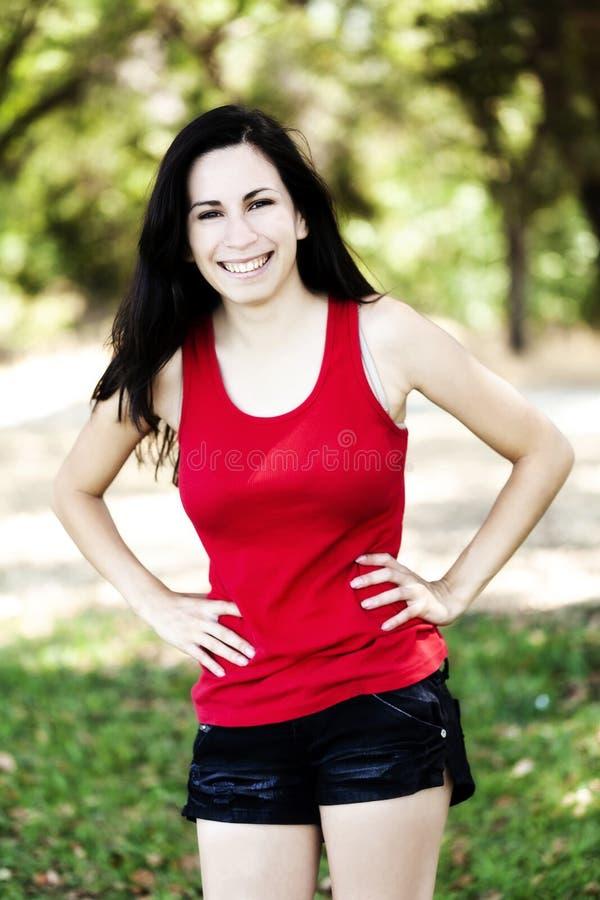 Att le ispanic Teen Woman Utomhus Red Top and Shorts royaltyfri foto