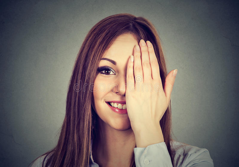 Att le kvinnan, med ögat, clossed vid handen, täckande del av hennes framsida fotografering för bildbyråer