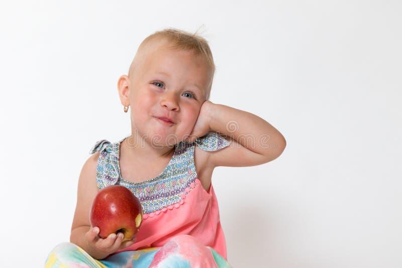 Att le litet barnflickan är sitta och rymma det röda äpplet royaltyfri foto