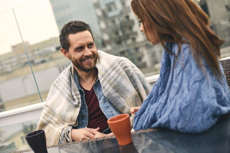 Att le mannen är att spendera tid med kvinnan på terrass arkivfoto