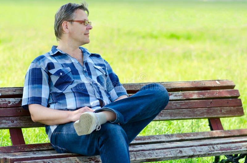 Att le mannen sitter på bänk utomhus royaltyfri foto
