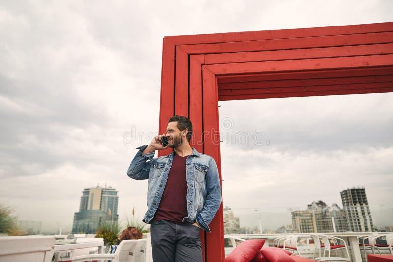 Att le mannen talar på mobiltelefonen royaltyfri bild