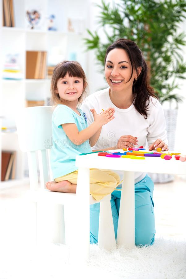 Att le modern hjälper lite dottern att hugga statyetter från plasticine Kreativitet för barn` s lycklig familj arkivbild