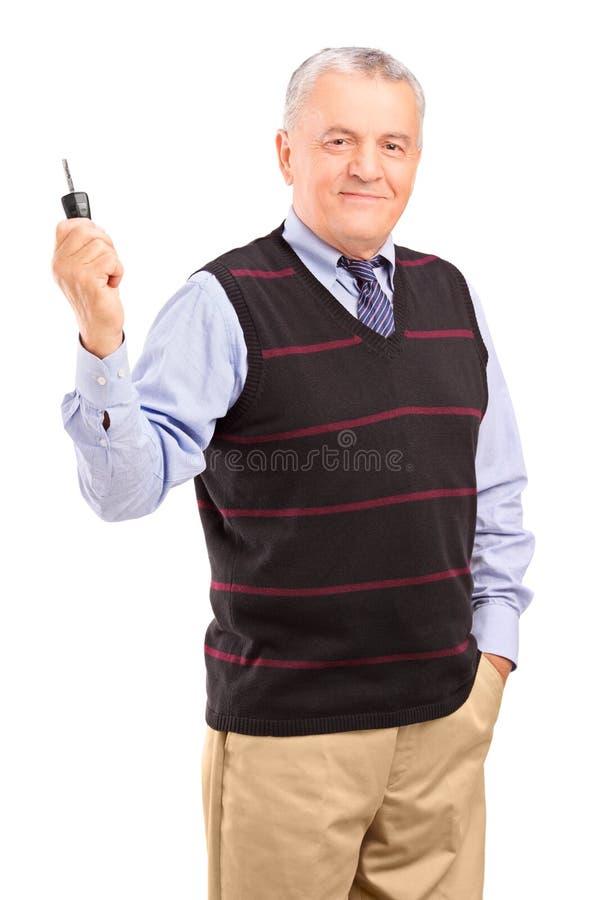 Att le mognar gentlemaninnehav en nyckel- bil arkivbild