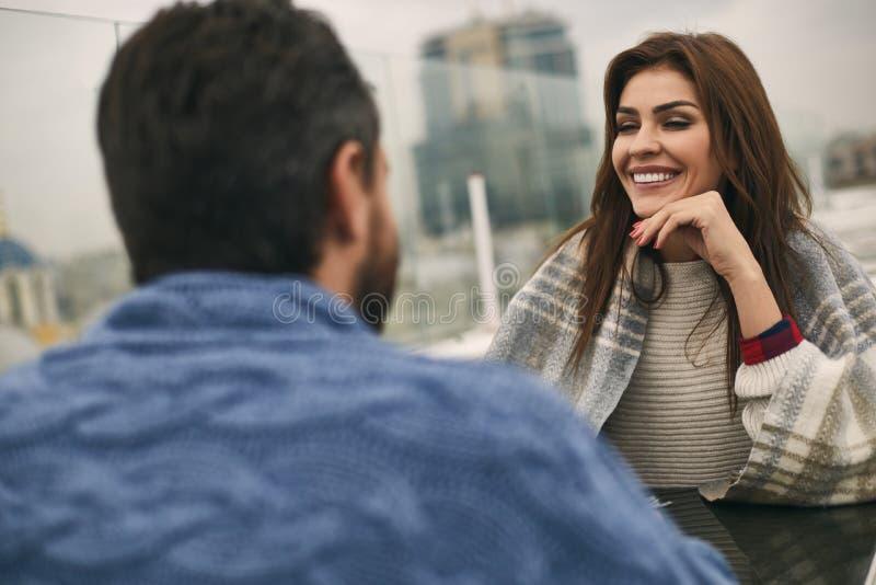 Att le par sitter i trevligt kafé utomhus arkivbild