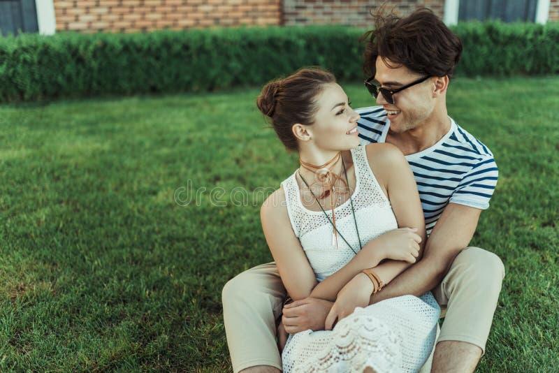 Att le par som kramar, medan spendera tid på, parkerar arkivfoto