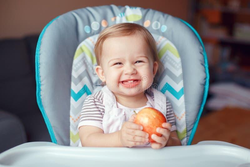 att le skratta Caucasian sammanträde för barnungeflicka i hög stol som äter äpplet, bär frukt arkivfoton