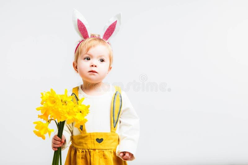 Att le som är gulligt, behandla som ett barn barnet i kanincostumewith en bukett av gula påskliljor på en vit bakgrund arkivfoto