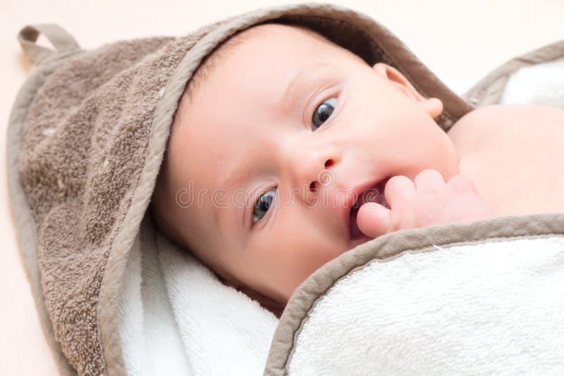 Att le som är litet, behandla som ett barn sätter ett finger i hennes mun royaltyfri foto