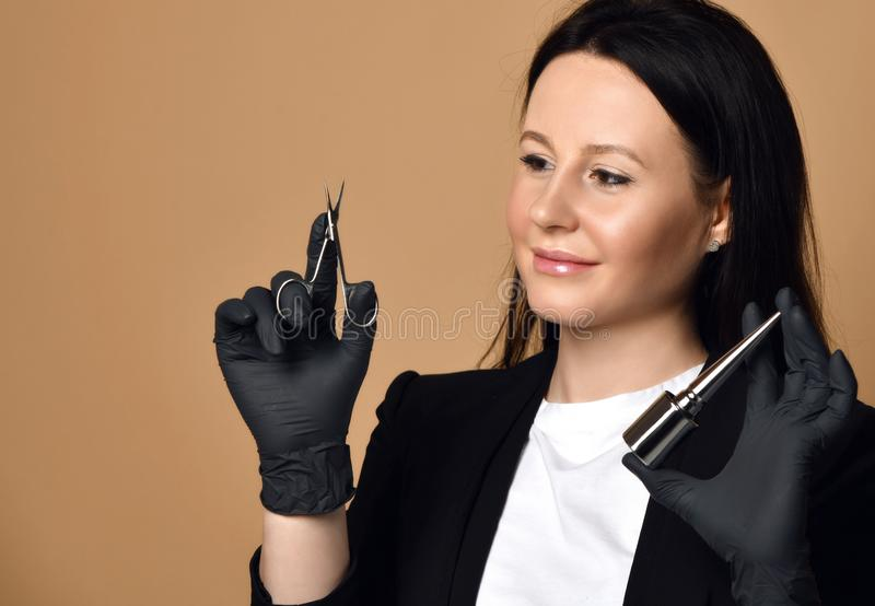 Att le spikar tekniker i svarta handskar med special sax och att spika fernissa royaltyfri foto