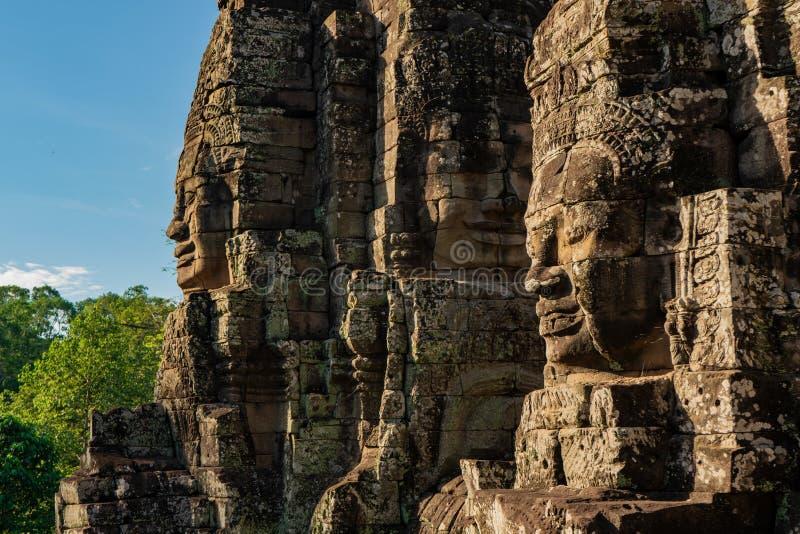 Att le stenen vänder mot av bayontemplet i Kambodja royaltyfri fotografi