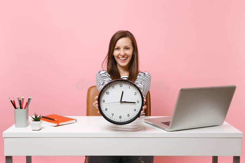 Att le stund för ringklocka för kvinnainnehavrunda sitter och att arbeta på projekt på det vita skrivbordet med den moderna PCbär royaltyfri fotografi