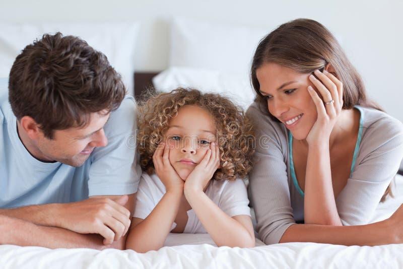 Att le uppfostrar att ligga på en säng med deras son arkivfoton