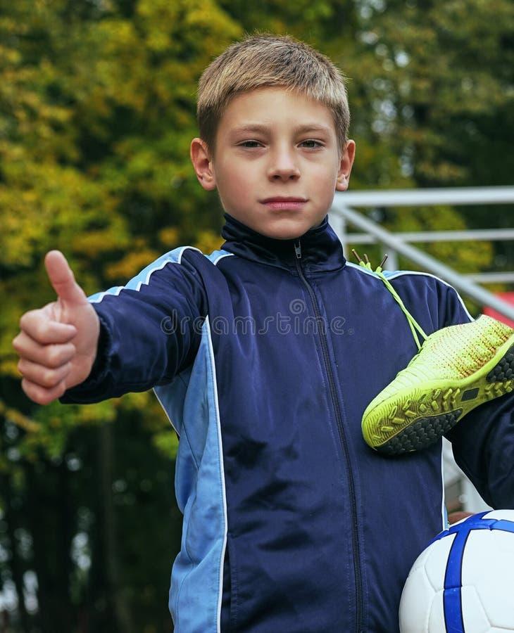 Att le visning för tonårs- pojke tummar upp med en fotbollboll i hans hand, och fotboll startar på skuldran mot royaltyfria foton