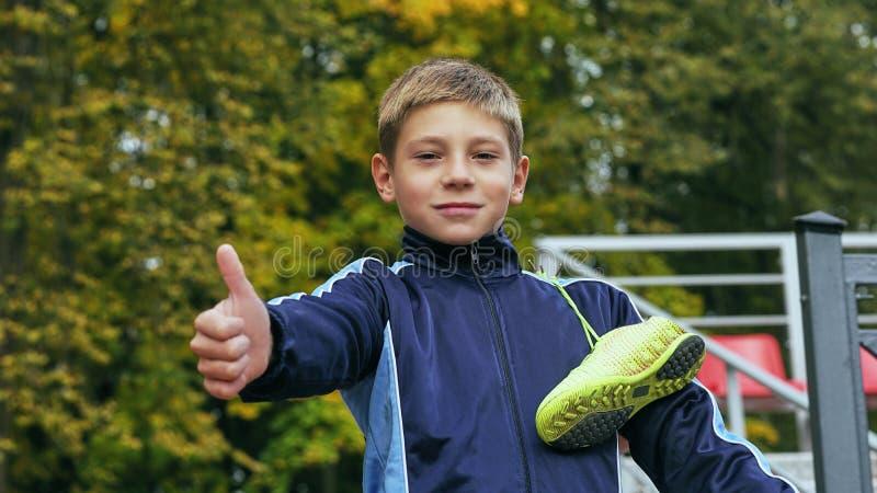Att le visning för tonårs- pojke tummar upp med en fotbollboll i hans hand, och fotboll startar på skuldran mot arkivbild