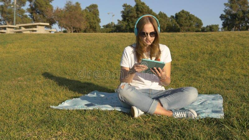 Att lyssna till musik från minnestavlan i parkerar på mattt royaltyfri foto
