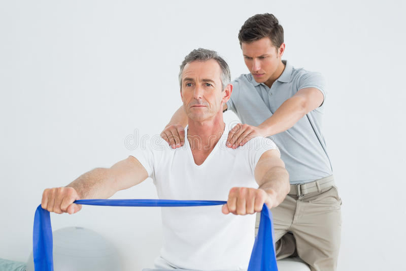Att massera för terapeut mans skuldran i idrottshallsjukhus royaltyfria foton