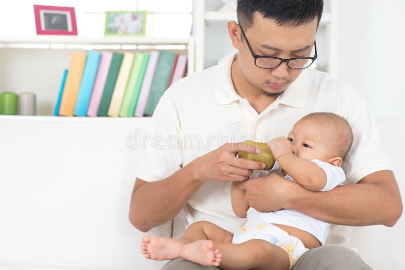 Att mata med flaska för fader behandla som ett barn arkivfoton