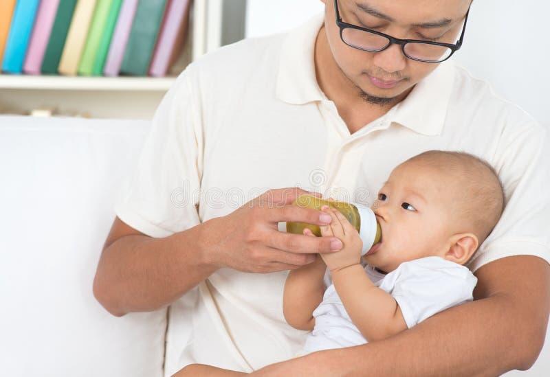 Att mata med flaska för fader behandla som ett barn hemma fotografering för bildbyråer