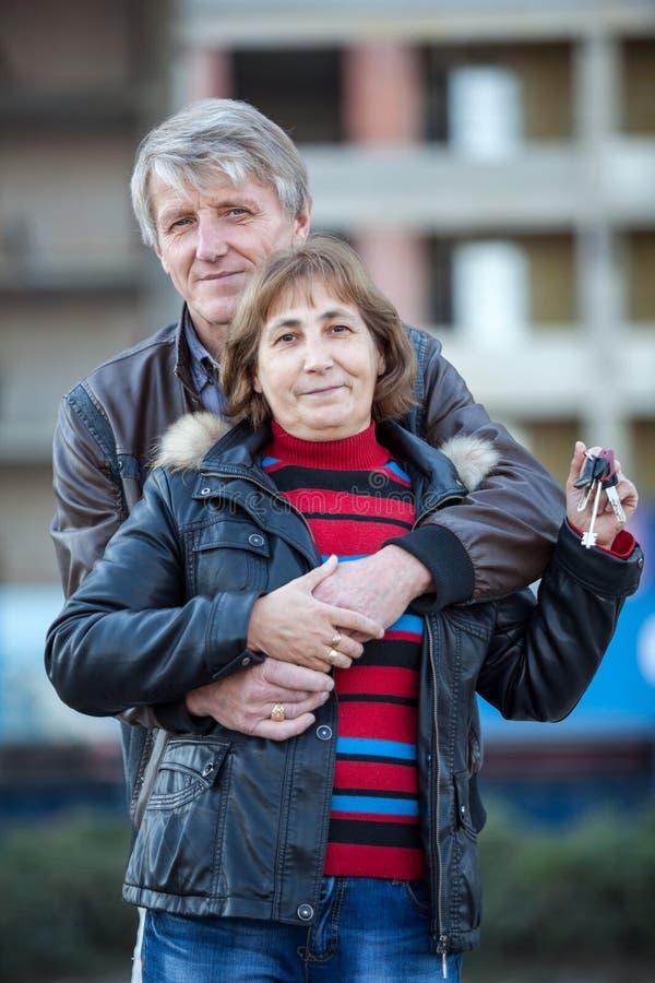 Att omfamna älska höga par med huset stämmer i hand arkivfoto