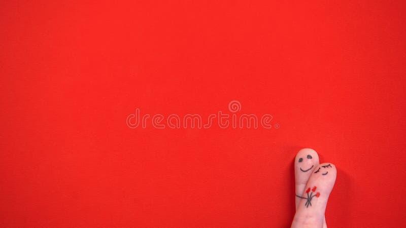 Att omfamna fingret vänder mot med målade blommor som isoleras på röd bakgrund, romantiker fotografering för bildbyråer